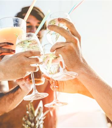 Group toasting their cocktails at the beach
