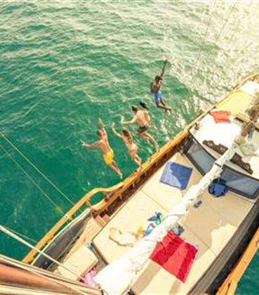 Group jumping off a sailboat into the ocean