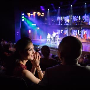 Couple enjoying a live show on a colorfully lit stage.