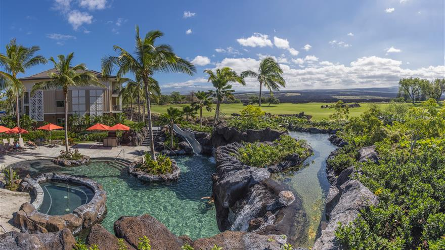 Overhead view of the pool surrounded by palm trees overlooking the Hawaiian countryside.