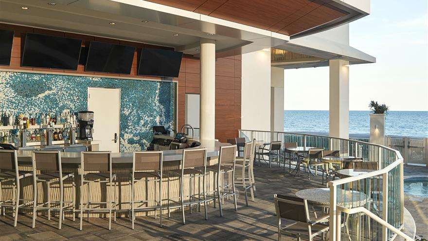 Outdoor bar with a view of the beach at Ocean Enclave by Hilton Grand Vacations located at Myrtle Beach, South Carolina.
