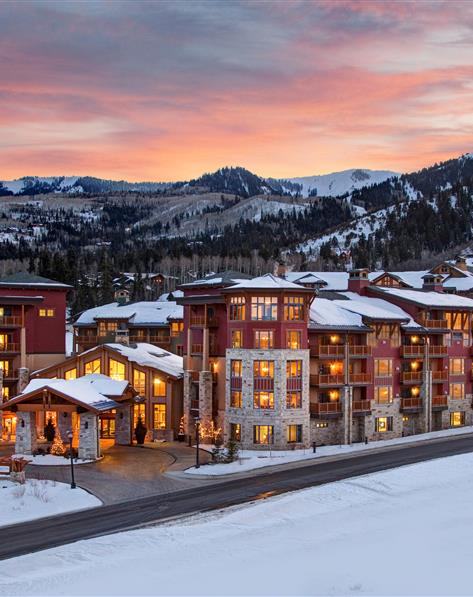 Exterior view of Sunrise Lodge covered in snow with snowcapped mountains in the background.