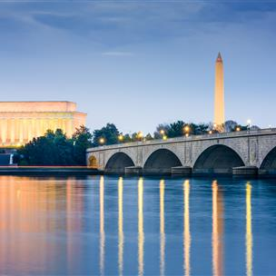 Washington Monument and Museum are reflected in a lake.