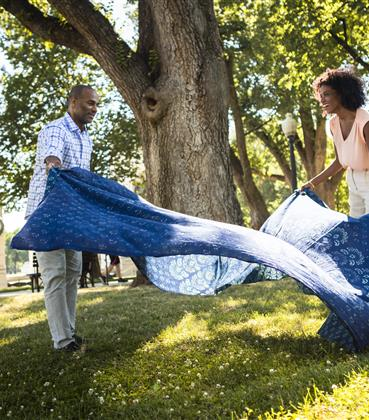 Couple laying out a blanket on a lawn for a picnic.