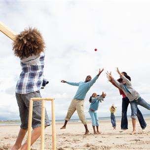 Family playing with a ball on the beach.
