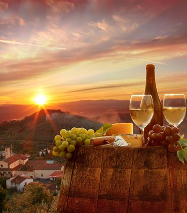 Wine glasses, cheese and grapes arrayed on a barrel in front of the sun setting over the Italian countryside.