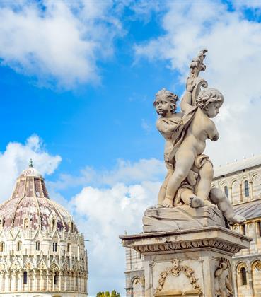 White stone statue in front of Italian architecture.