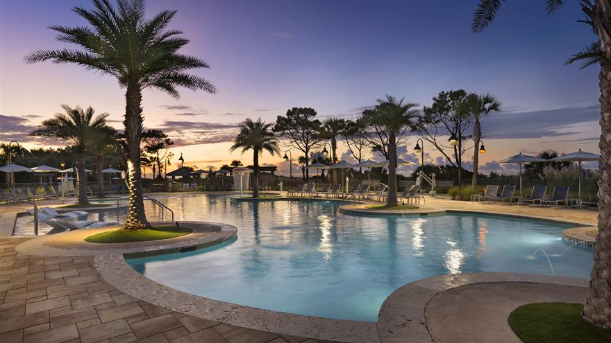 Pool and courtyard surrounded by palm trees with the sun setting in the background at Ocean Oak Resort by Hilton Grand Vacations located at Hilton Head, South Carolina.