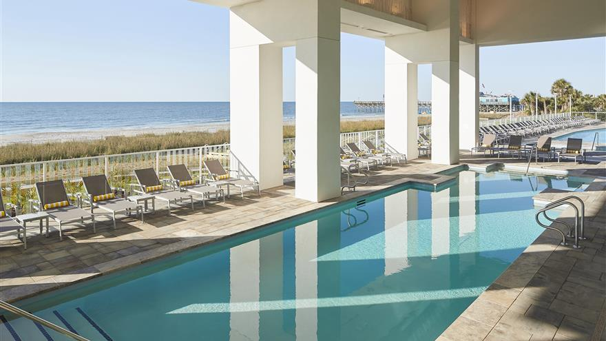 Pool with ocean in the distance at Ocean Enclave by Hilton Grand Vacations located at Myrtle Beach, South Carolina.