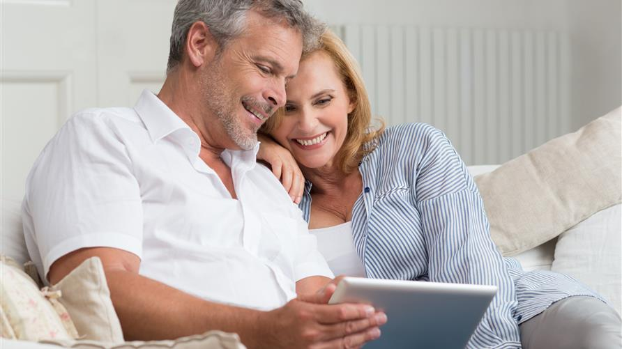 A mature couple cuddling on couch while looking at a tablet.