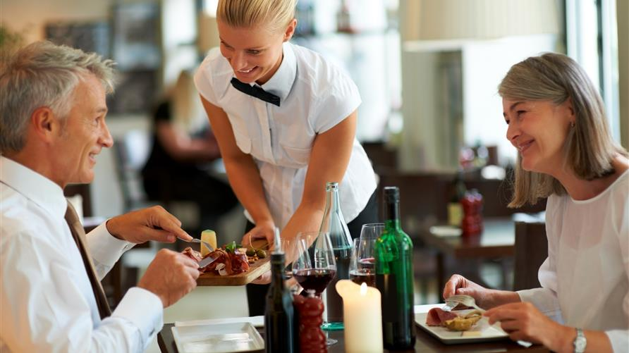 Wait staff serving mature couple at Hilton Grand Vacations