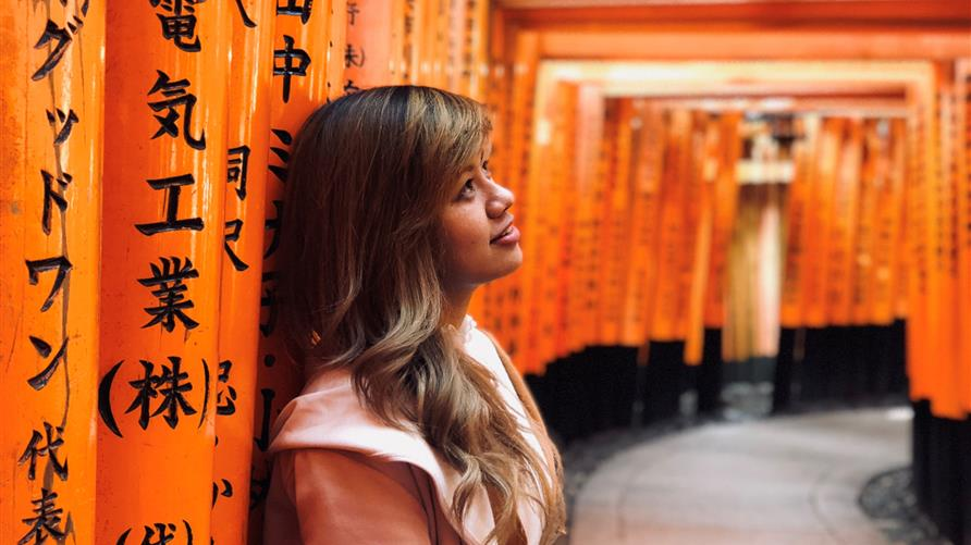 A woman gazing at an artistic hallway in Japan.