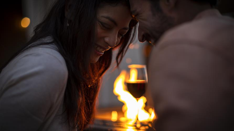 Couple cuddling by fire with wine