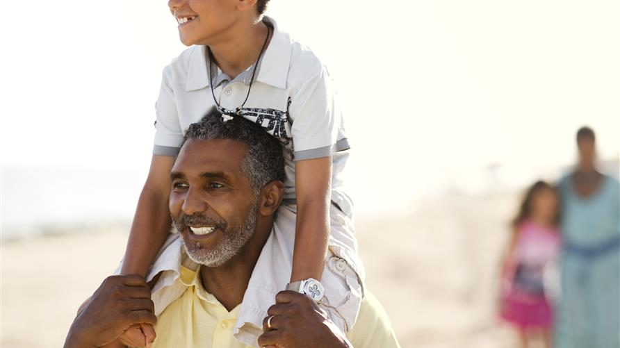 Father, with son on his shoulders, smiling and walking on the beach.