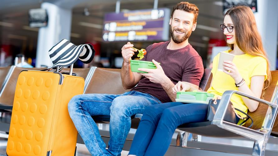Young couple eating at an airport on a layover.