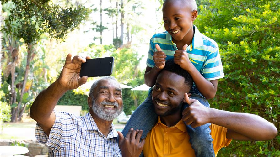 Dad, grandfather and son taking a selfie on a multigenerational vacation in Orlando, Florida.