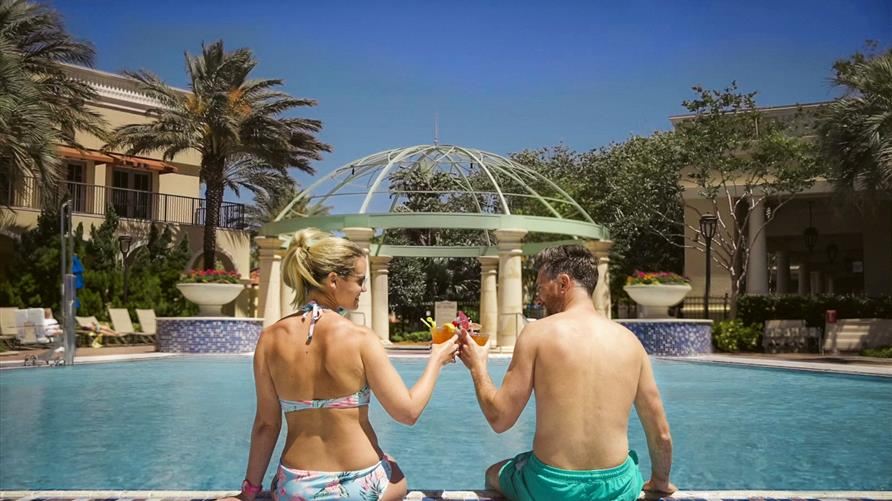 A couple poolside at Hilton Grand Vacations Tuscany Village in Orlando, Florida.