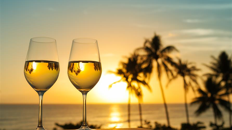Two glasses of wine with the Hawaiian sunset in the background.