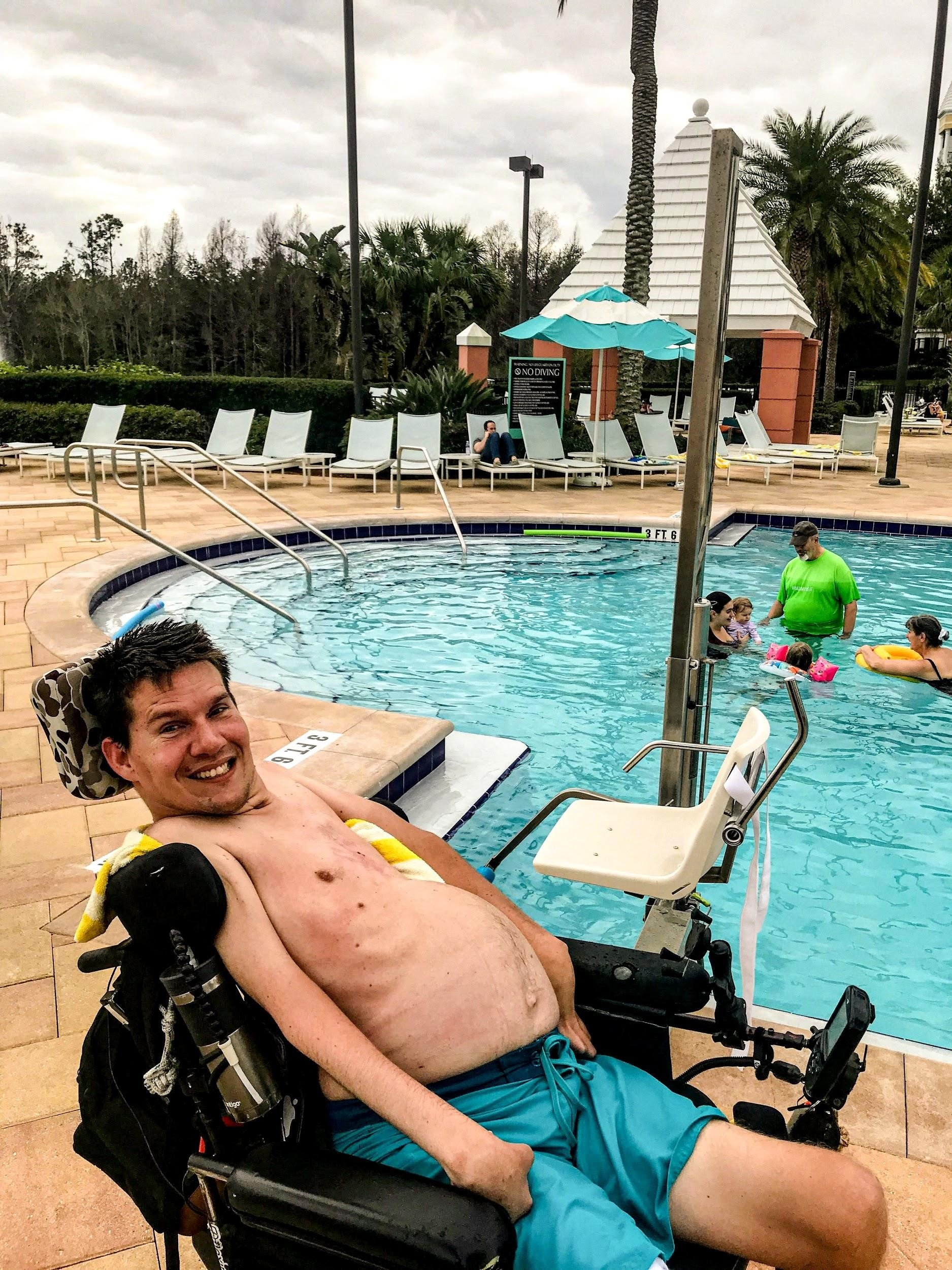 A Hilton Grand Vacations Owner in a wheel chair excited about the handicap pool lifts at the Hilton Grand Vacations at SeaWorld resort pool.