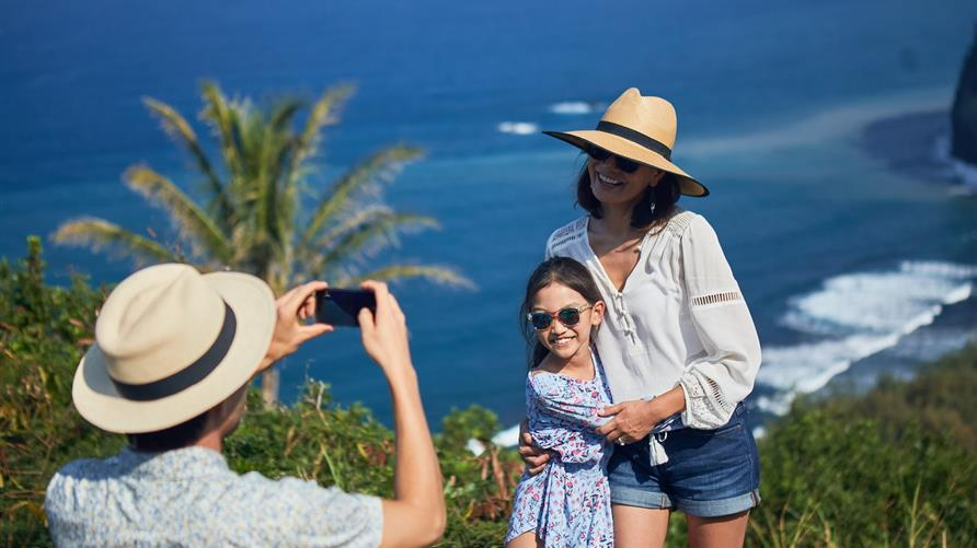 Family taking a picture while on vacation in an island paradise.