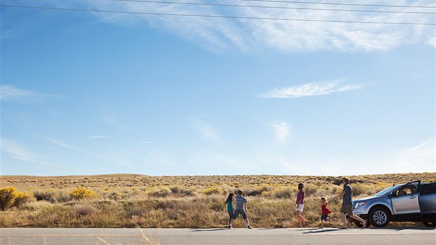 A family stretching their legs on the side of the open road.
