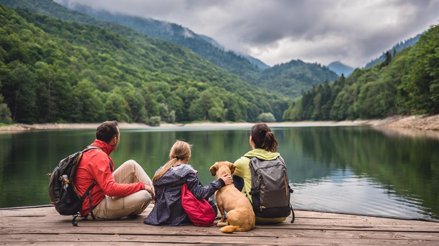 A family, on an outdoor adventure trip, sitting on a dock gazing at a mountain lake.