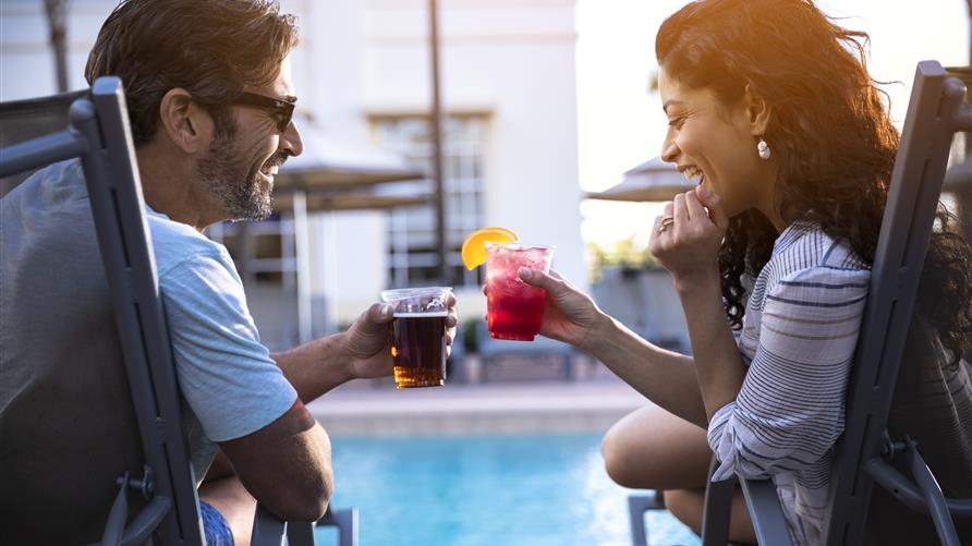 A happy couple toasting poolside at a Hilton Grand Vacations Club in Orlando, Florida.