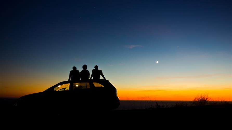 A group of people star gazing on the roof of a car.
