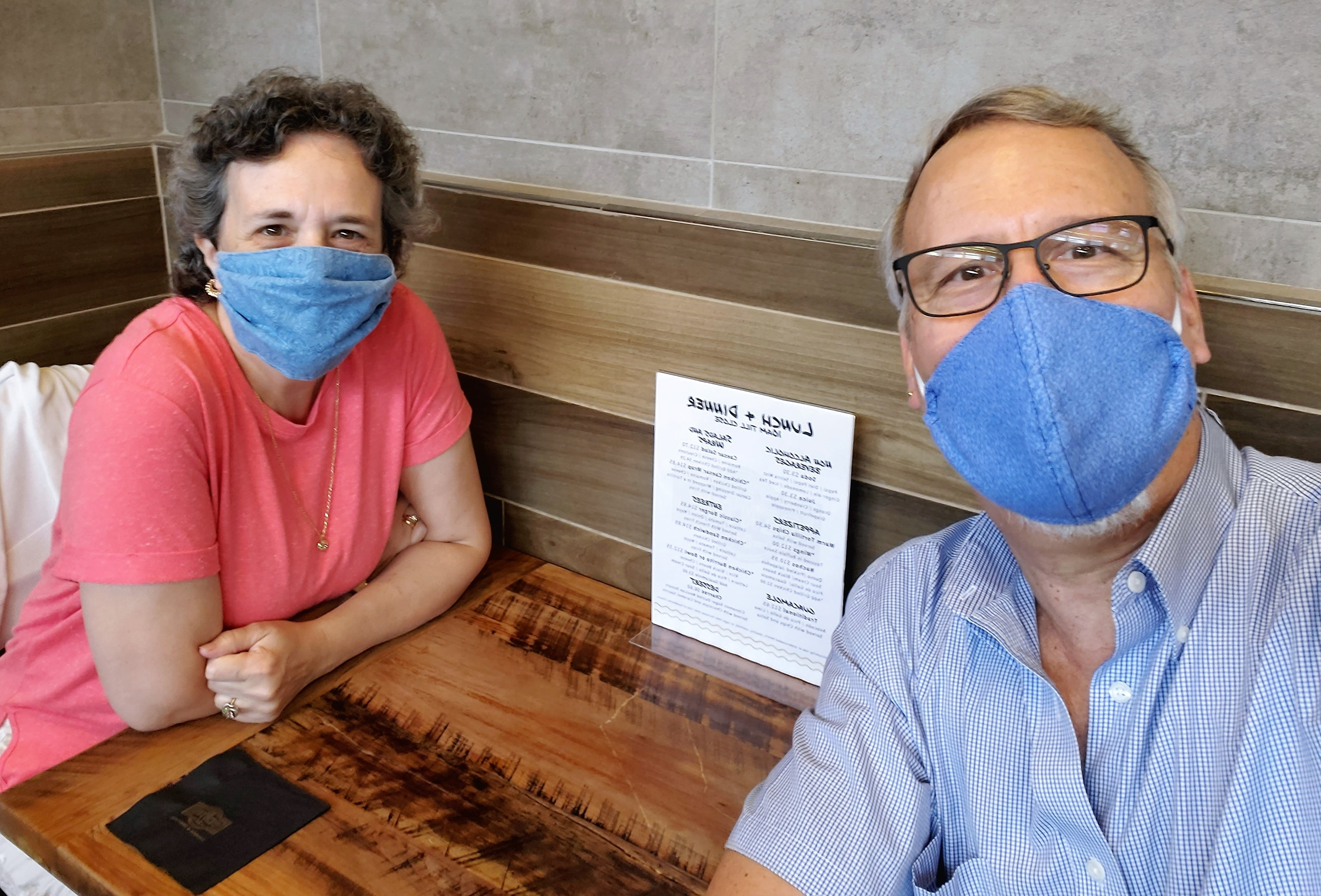 A mature couple wear face masks at the air-port on their way to vacation at Sunrise Lodge a Hilton Grand Vacations Club in Park City, Utah.