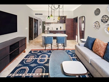 Shot of suite interior at La Pacifica by Hilton Club, including fully equipped kitchen, dining table and living room.