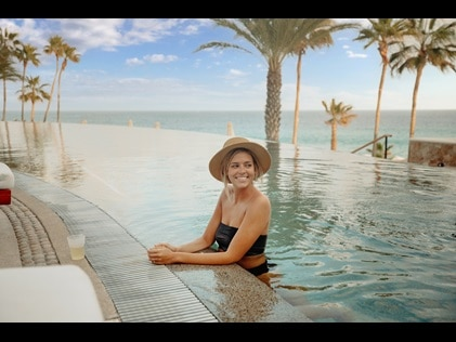 Woman smiling while enjoying the infinity pool at the new Los Cabos resort, La Pacifica by Hilton Club.