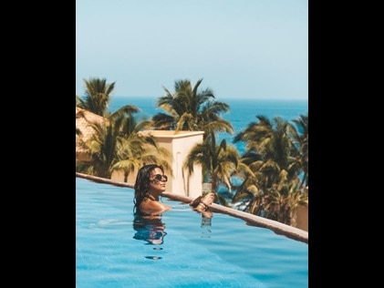 A woman looking out to sea in an infinity pool at Hilton Grand Vacations in Los Cabos, Mexico.