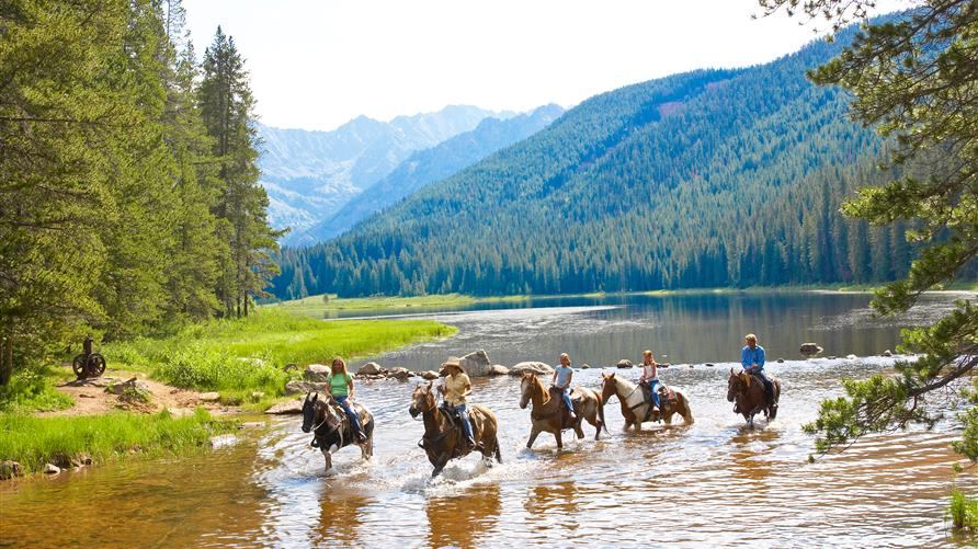A group of people enjoying horseback riding on an guided adventure travel trip with Hilton Grand Vacations.