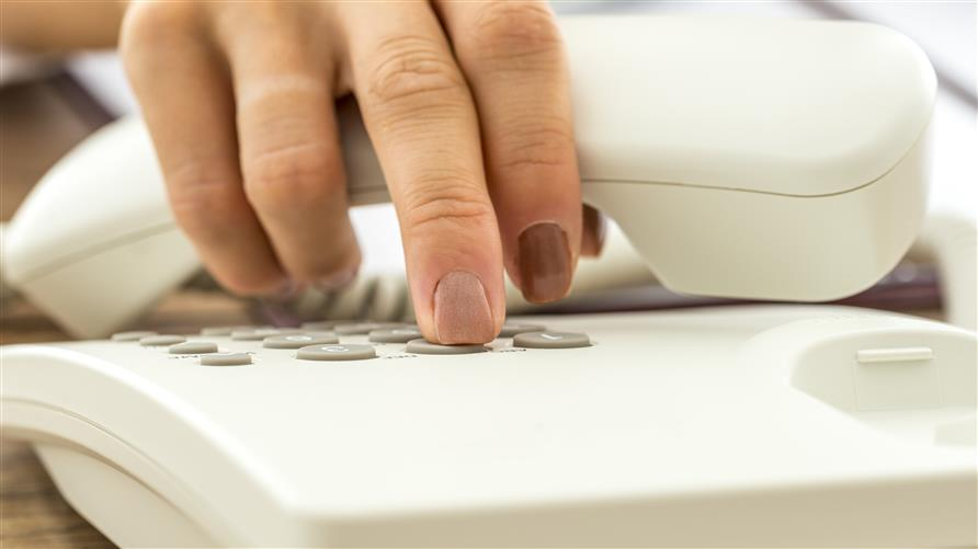 Woman's hand dialing on a land line.