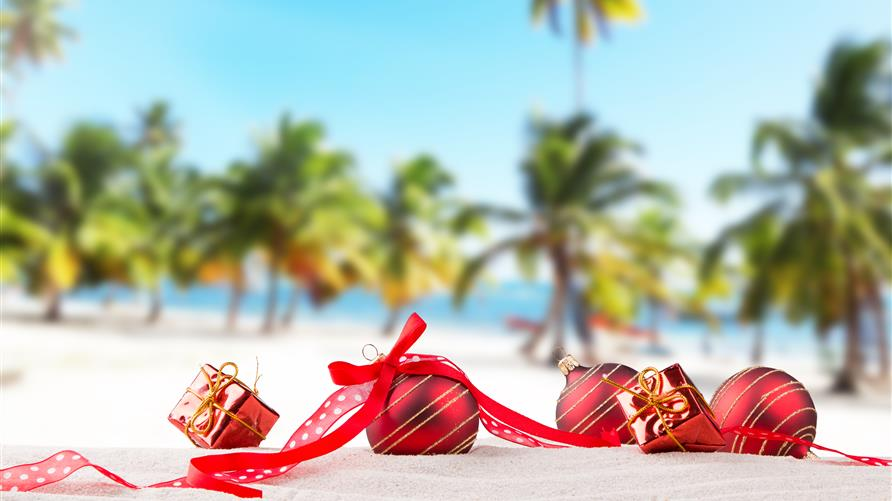 Christmas ornaments laying on the beach with palm trees in the background.