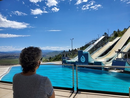 Woman admiring Olympic Park while on vacation at Sunrise Lodge, a Hilton Grand Vacations Club in Park City, Utah.