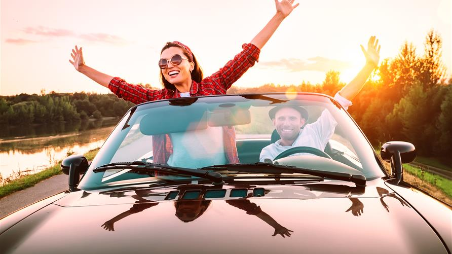 Excited couple riding in a convertible with the top down and their arms raised headed out for a long-weekend vacation.