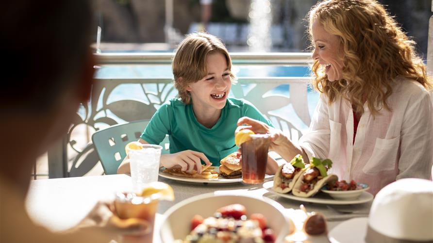 Happy family enjoying lunch poolside at Hilton Grand Vacations at SeaWorld in Orlando, Florida.