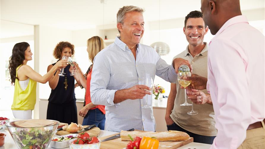 A group of mature friends gathered in their Hilton Grand Vacations resort kitchen socializing and smiling.