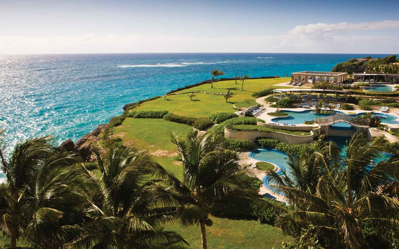 Aerial view of the pool complex overlooking the ocean at Hilton Grand Vacations at The Crane in St. Philip, Barbados.