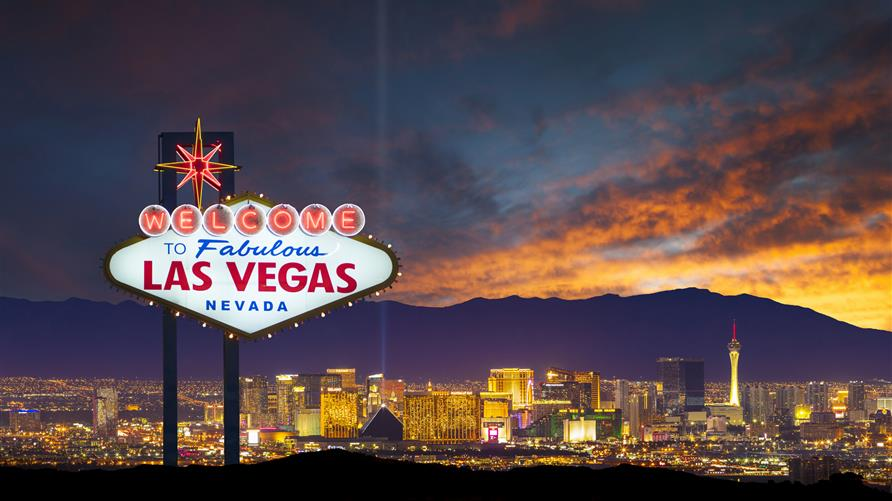 The sunset sinking behind the mountains and the city lights behind the Las Vegas sign.