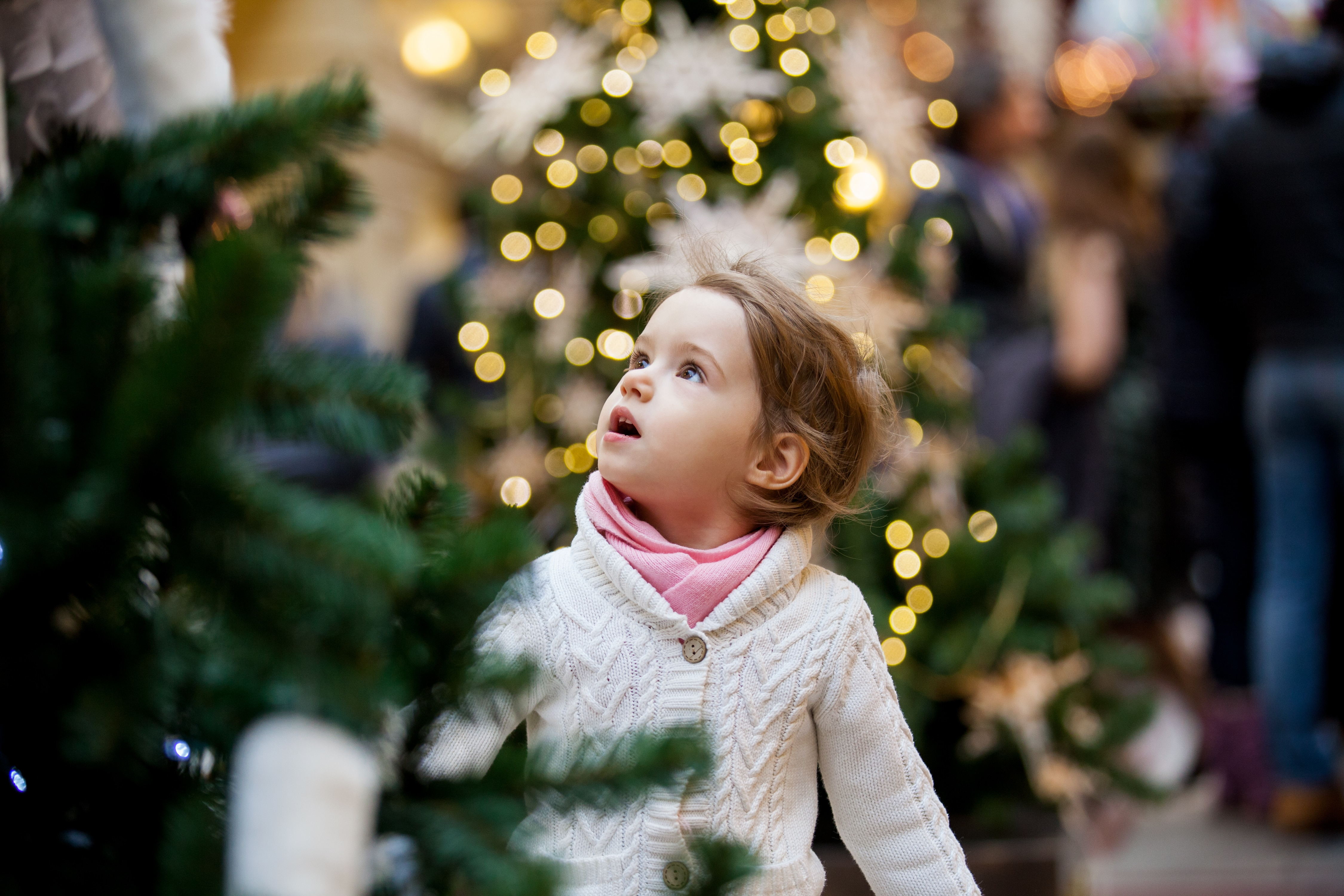 Little girl looking up in awe at Christmas lights.
