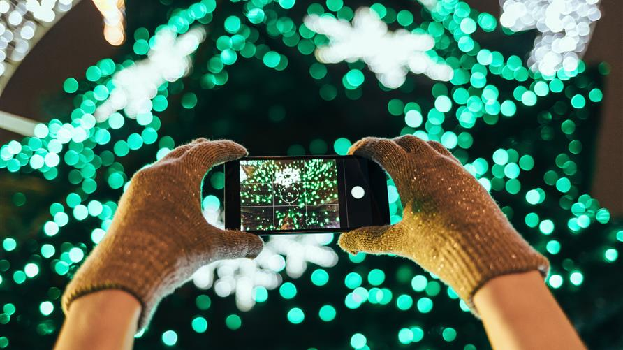 Close up shot of a woman in gloves taking pictures of a Christmas light display with a smart phone.