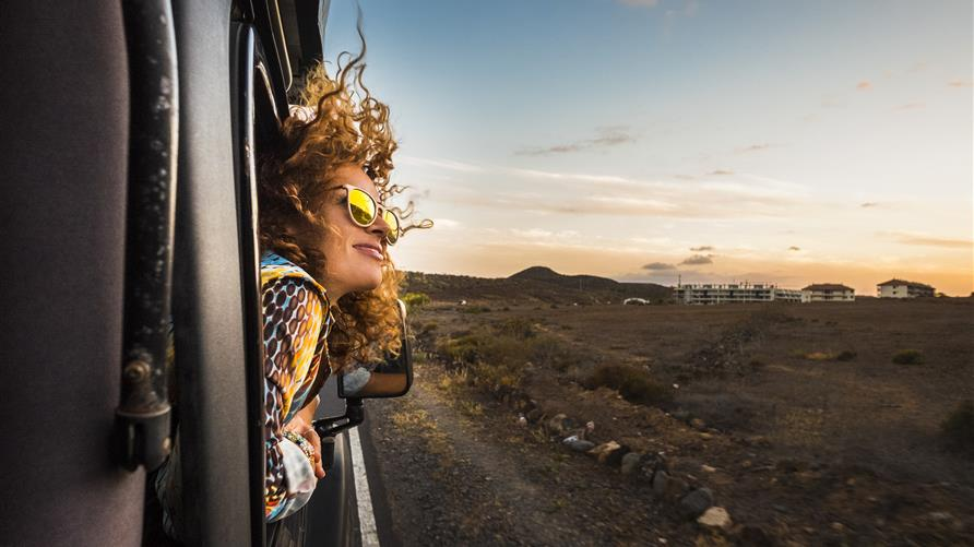 Woman with curly hair  blowing in the wind while she gazes at the sky from the car window.