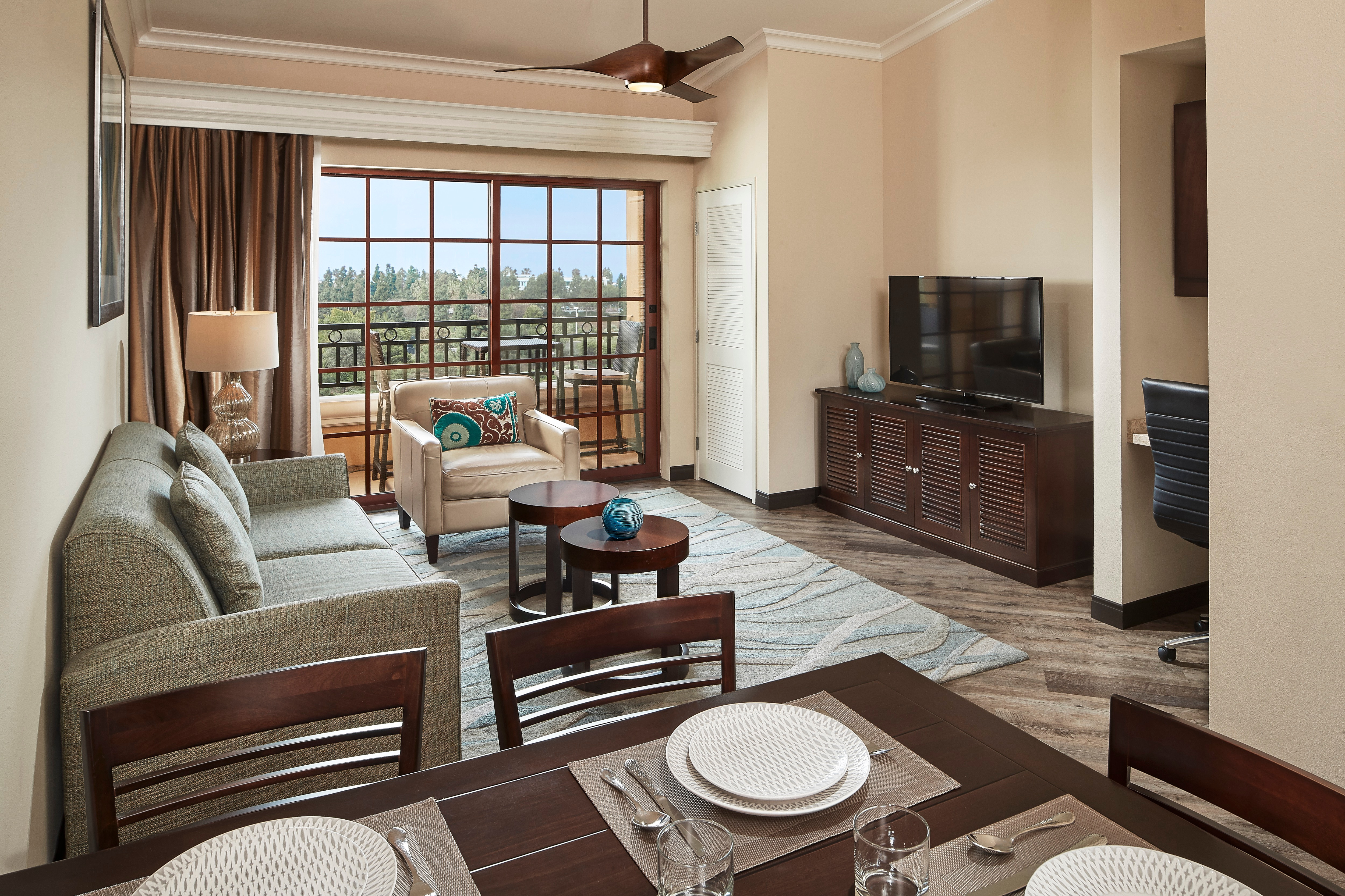 Hilton Grand Vacations suite interior, including dinning space, living room and balcony.