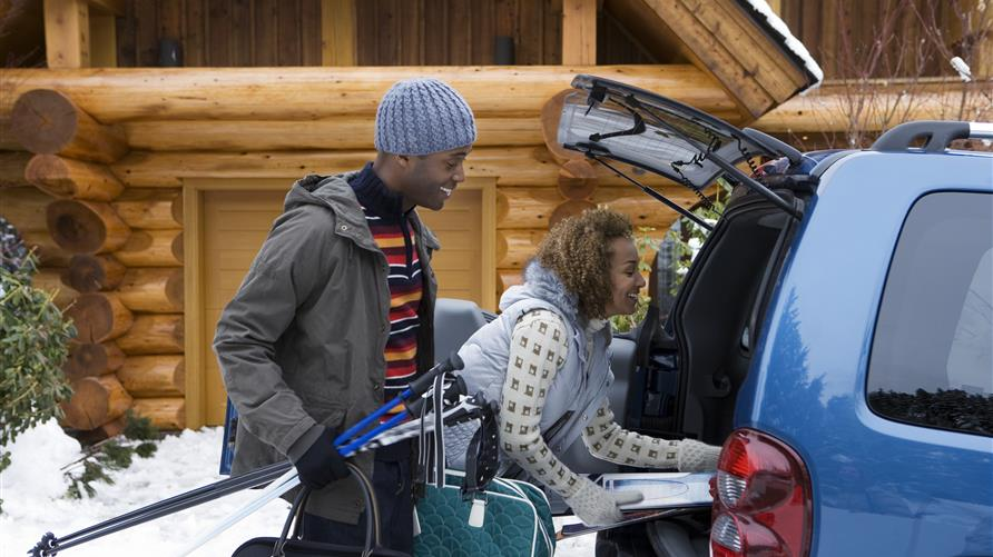 Couple excitedly packing their car for a Christmas vacation.