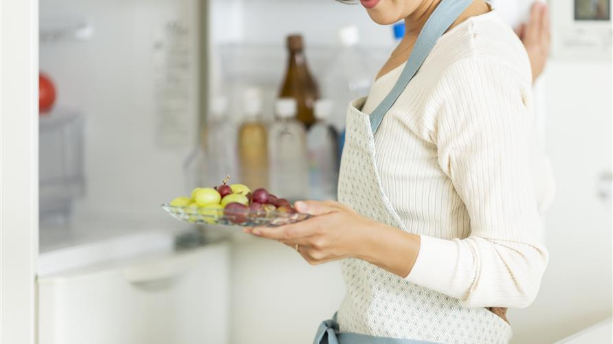 Woman happily pulling fresh fruit out of a refrigerator.