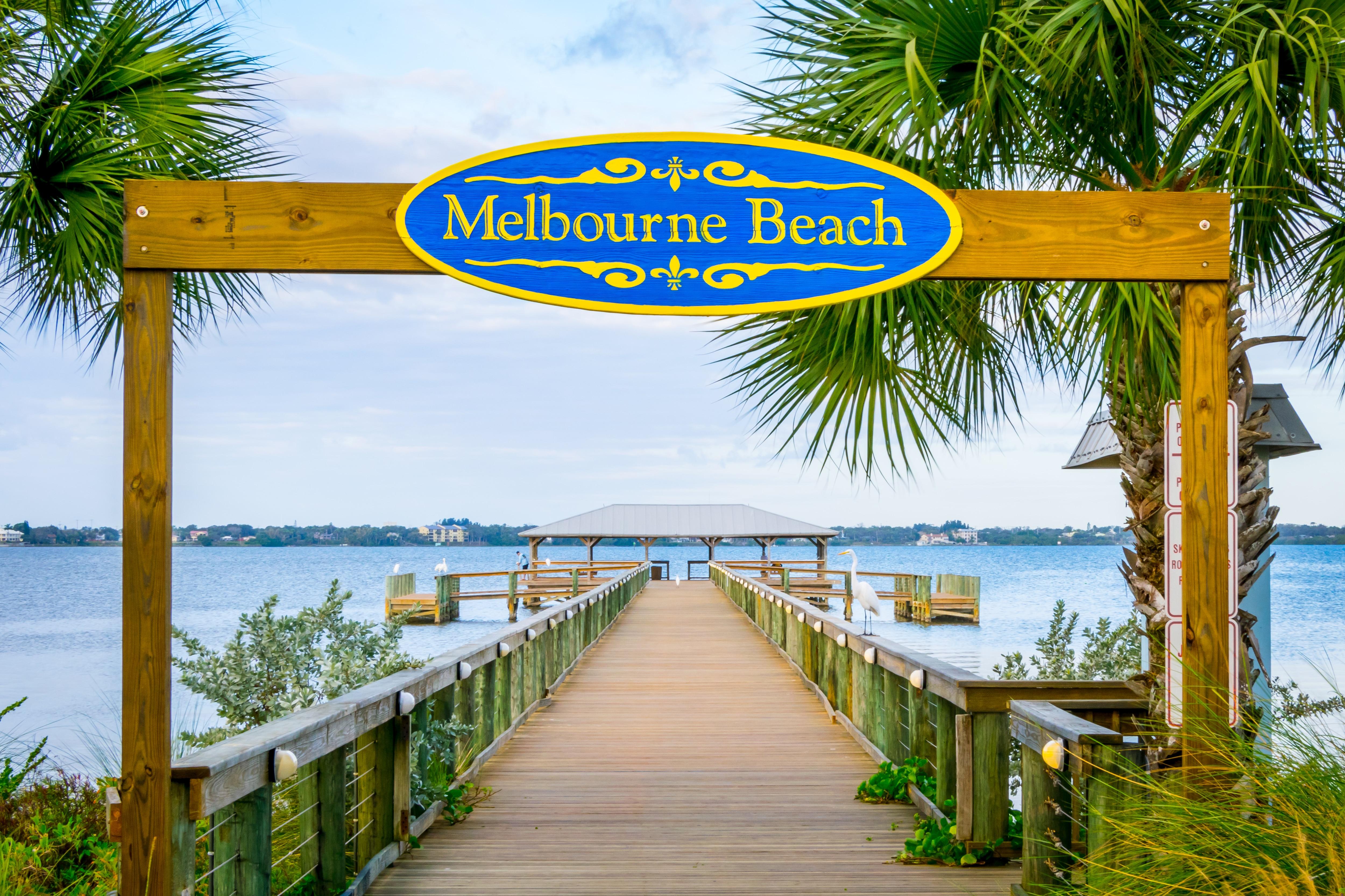 Melbourne Beach sign and pier in Melbourne Beach, Florida.