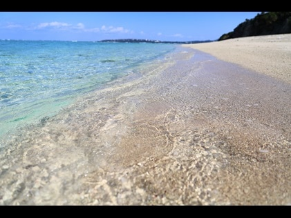 Crystal clear water washing ashore a quiet beach.