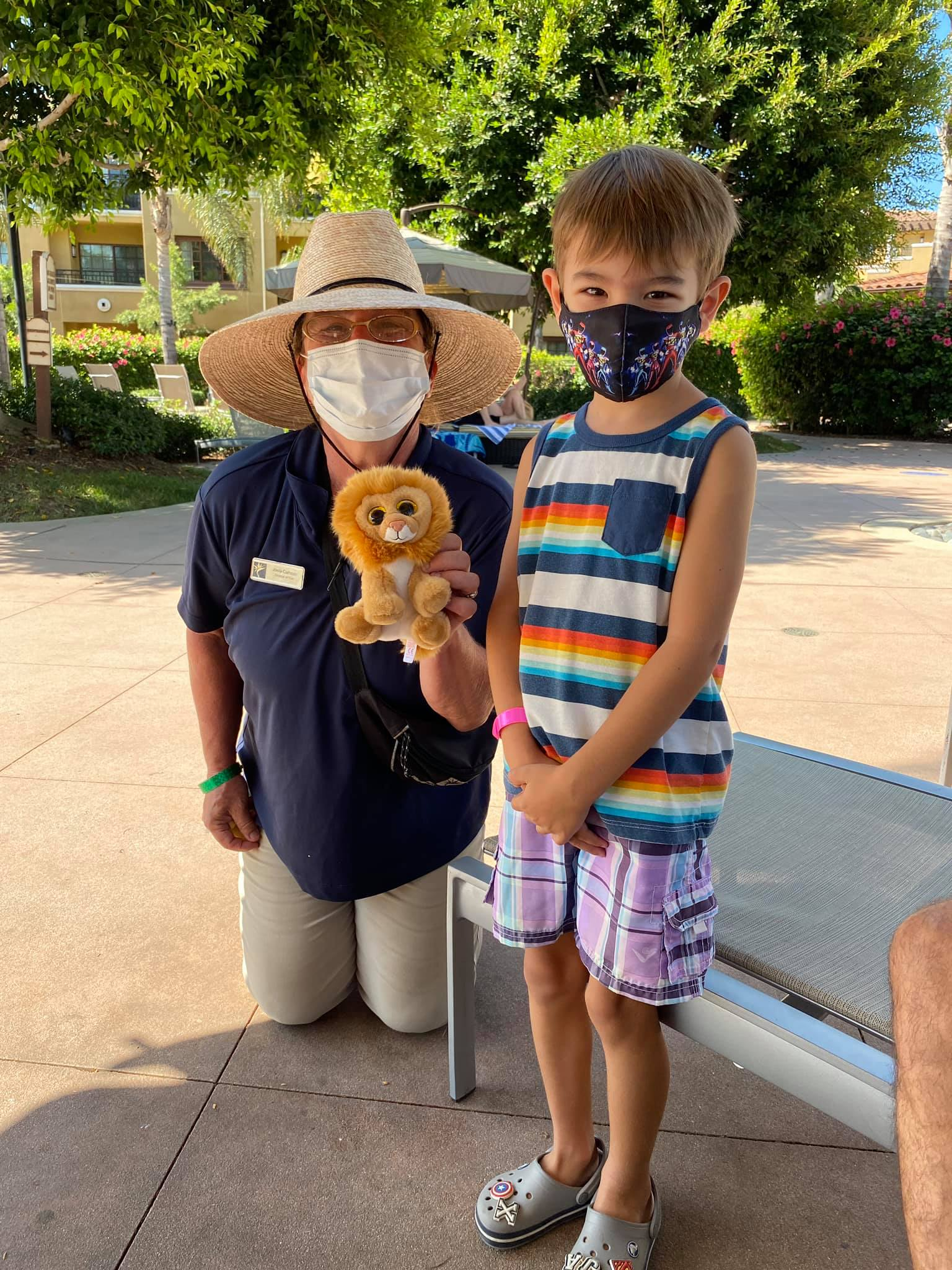 Little boy posing with Hilton Grand Vacations at MarBrisa team member.